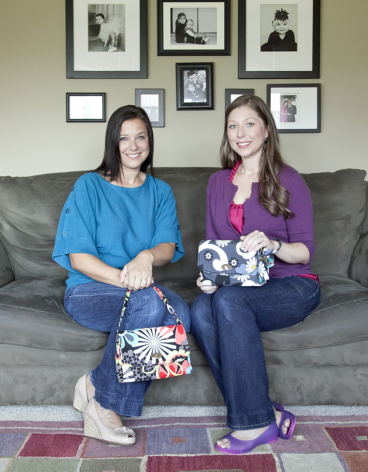 Lyssa Surface (L) and Jessica Schifman (R) show off their diaper clutch designs.